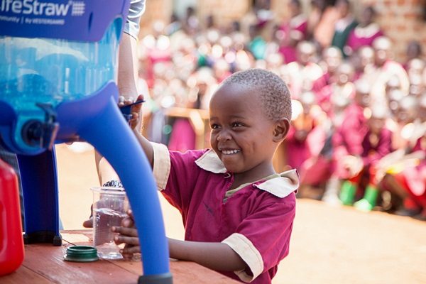 a pupil from exodus academy pours a glass of safe water from the new lifestraw community purifier replacing dirty water from a local stream